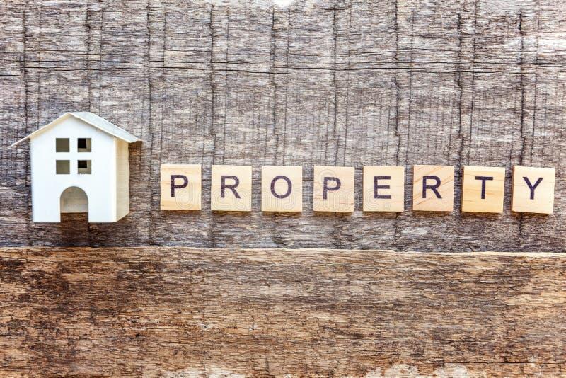 La casa miniatura del modello del giocattolo con la PROPRIETÀ dell'iscrizione segna la parola con lettere su fondo di legno fotografie stock