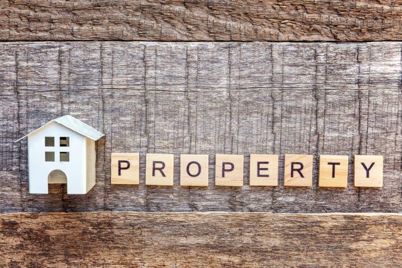 La casa miniatura del modello del giocattolo con la PROPRIETÀ dell'iscrizione segna la parola con lettere su fondo di legno immagine stock libera da diritti