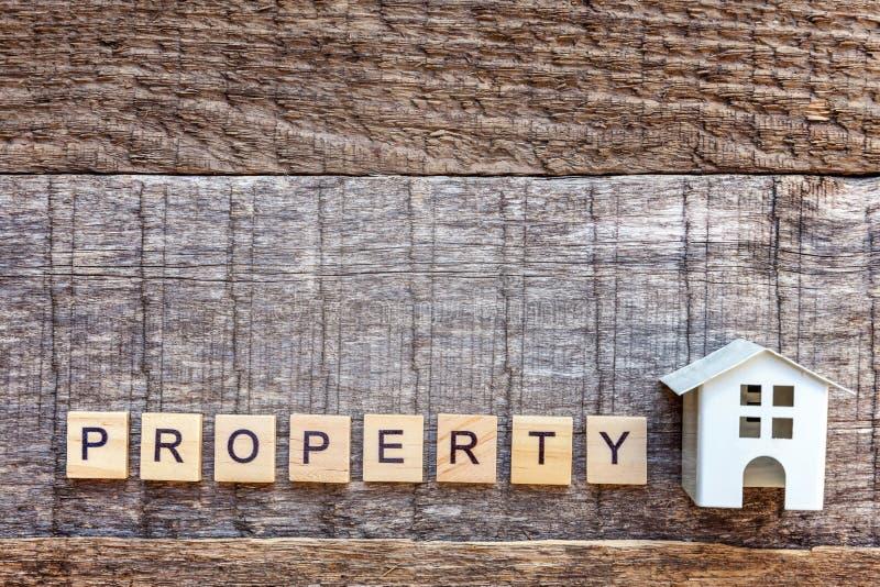 La casa miniatura del modello del giocattolo con la PROPRIETÀ dell'iscrizione segna la parola con lettere su fondo di legno immagine stock