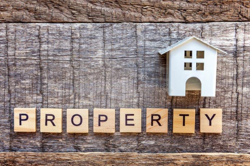 La casa miniatura del modello del giocattolo con la PROPRIETÀ dell'iscrizione segna la parola con lettere su fondo di legno fotografia stock libera da diritti