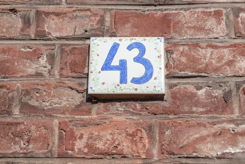 La casa número cuarenta y tres 43 esmaltó la baldosa cerámica con los dígitos y los modelos de flores azules imagenes de archivo