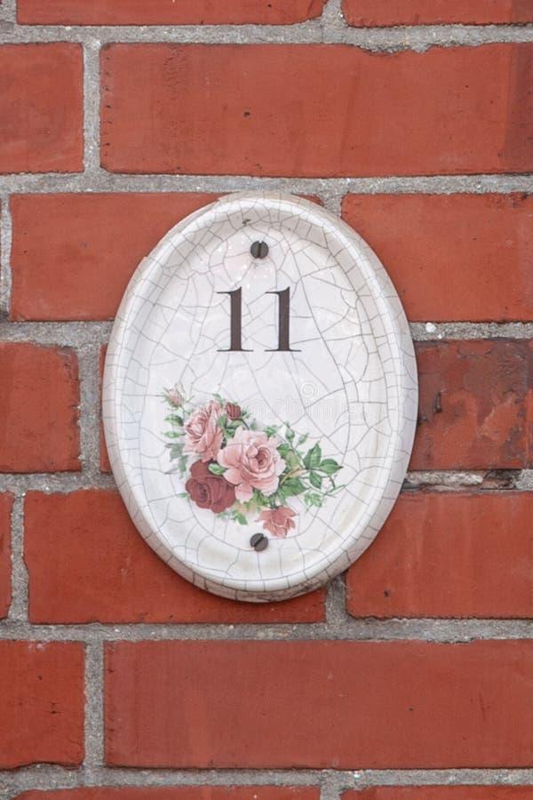 La casa número once 11 esmaltó la baldosa cerámica con los dígitos y los modelos de flores negros foto de archivo
