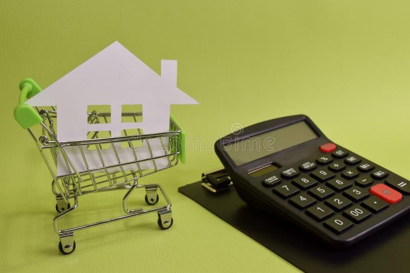 La casa puso en un carro de la compra y una calculadora en el escritorio Ahorros para el hogar, las casas de compra, las casas de foto de archivo libre de regalías