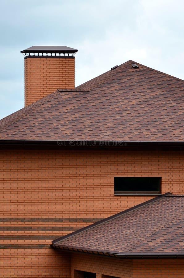 La casa se equipa de la techumbre de alta calidad de las tejas del betún de las tablas Un buen ejemplo de la techumbre perfecta E imagenes de archivo