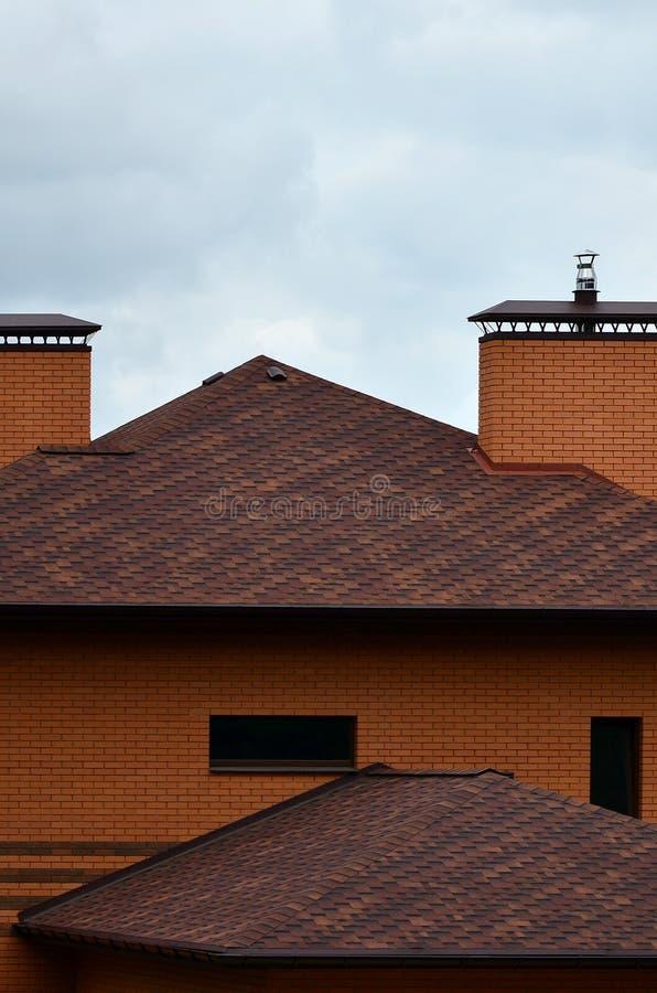 La casa se equipa de la techumbre de alta calidad de las tejas del betún de las tablas Un buen ejemplo de la techumbre perfecta E fotografía de archivo libre de regalías