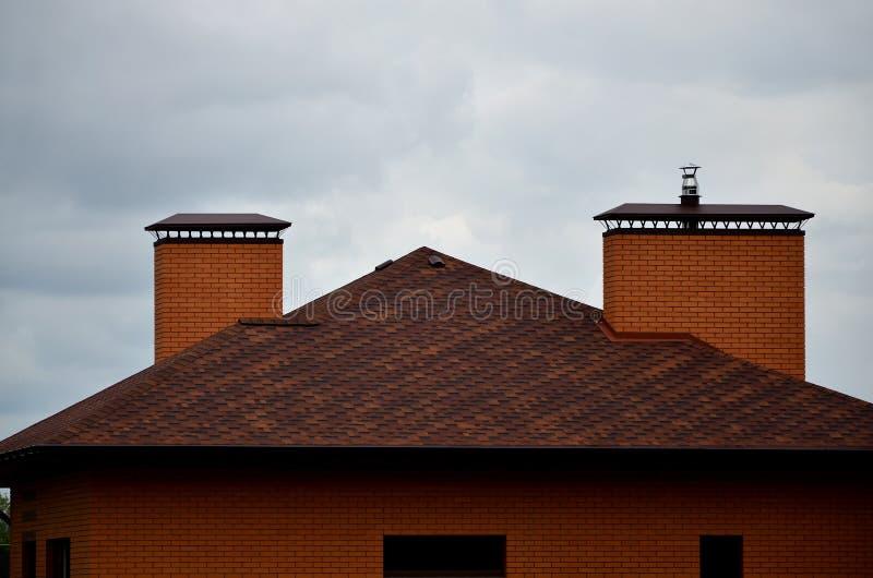 La casa se equipa de la techumbre de alta calidad de las tejas del betún de las tablas Un buen ejemplo de la techumbre perfecta E imagen de archivo