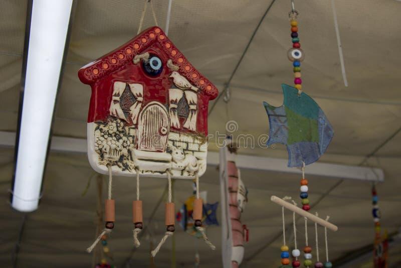 la casa y el vidrio de pescados coloreados azules se están vendiendo como ornamento decorativo Colgante en los soportes del techo fotos de archivo libres de regalías
