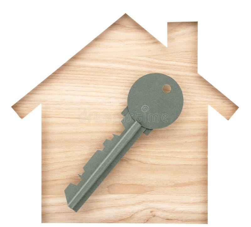 La casa y la llave formaron el recorte de papel en la madera de construcción de madera natural imagen de archivo
