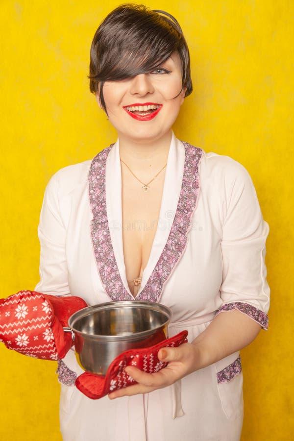 La casalinga caucasica prepara un pasto i supporti castana in un accappatoio con una pentola ed i supporti di vaso su un backgro  fotografia stock libera da diritti
