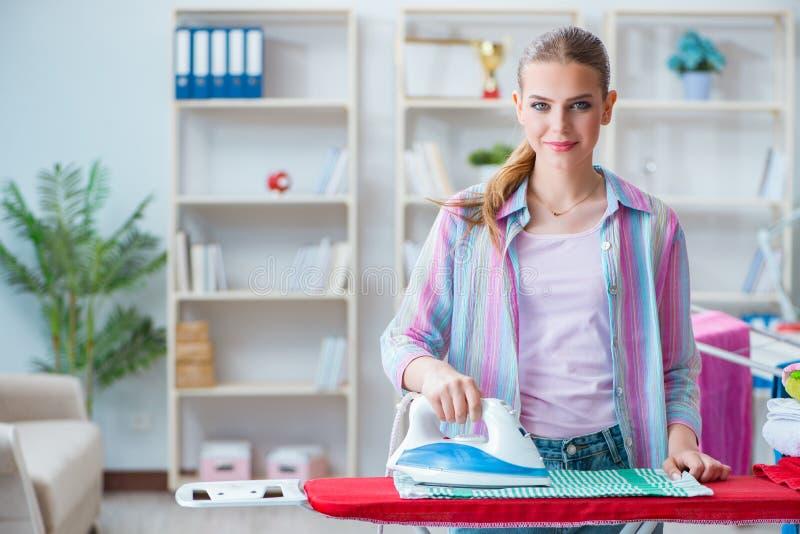 La casalinga felice che fa rivestire di ferro a casa immagini stock libere da diritti