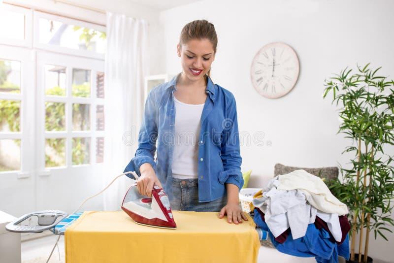 La casalinga felice e sorridente gode di nel rivestire di ferro i suoi vestiti immagini stock libere da diritti