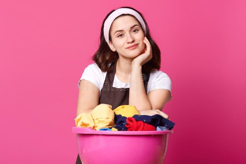 La casalinga graziosa della giovane donna con il bacino rosa in pieno delle cose lavate pulite, indossa la banda dei capelli, la  fotografia stock