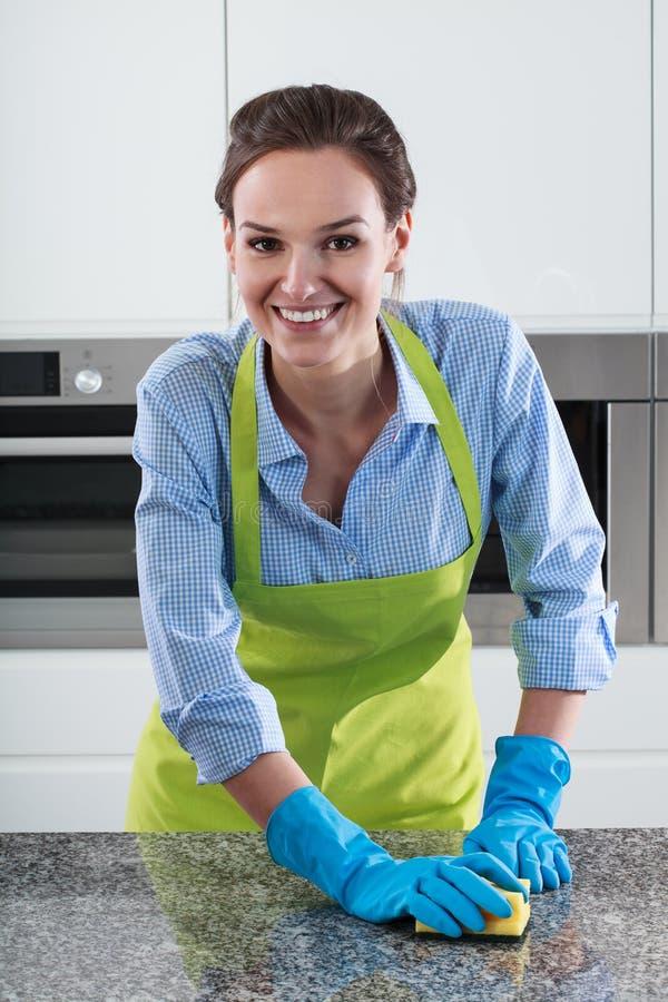 La casalinga sorridente pulisce il piano di lavoro fotografie stock libere da diritti
