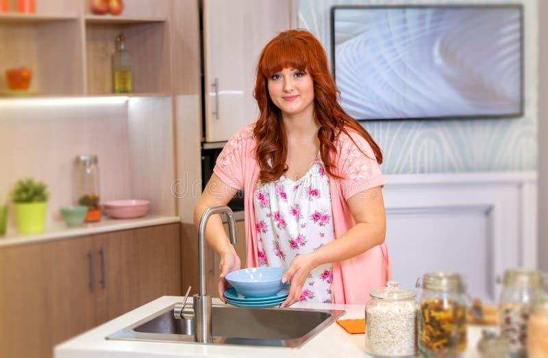 La casalinga sta andando lavare i piatti immagini stock