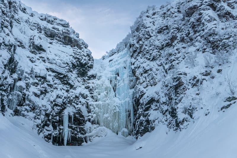 La cascada congelada Njupeskär con el escalador en su manera abajo foto de archivo libre de regalías