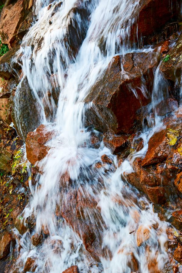 La cascada en la roca roja foto de archivo