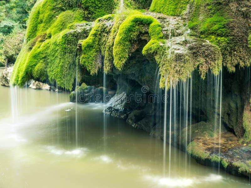La cascada hermosa unic de Bigar por completo del musgo verde foto de archivo
