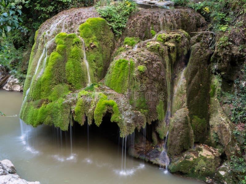 La cascada hermosa unic de Bigar por completo del musgo verde fotos de archivo