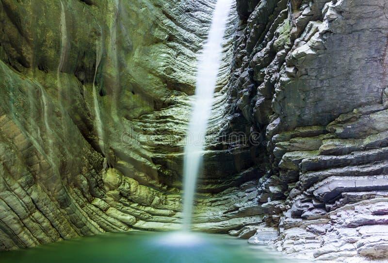 La cascade dans une roche avec de l'eau brillant s'est allumée par l'eau de lumière du soleil photographie stock