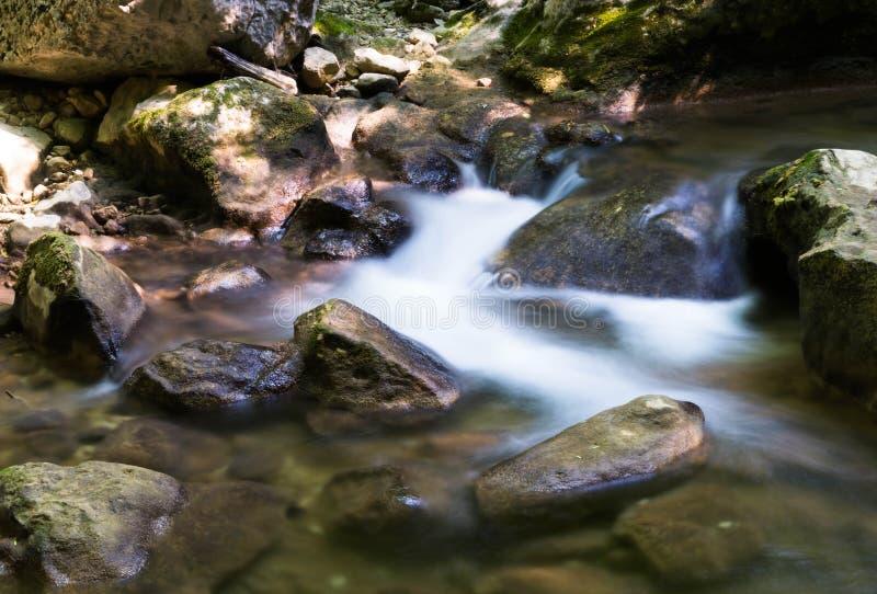 La cascata cade sopra le rocce muscose fotografia stock