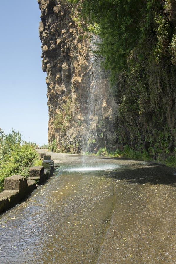 La cascata sulla vecchia strada chiusa sull'orlo della scogliera rocciosa fra Ponta fa il solenoide e Jardim guasta, isola del Ma fotografie stock libere da diritti