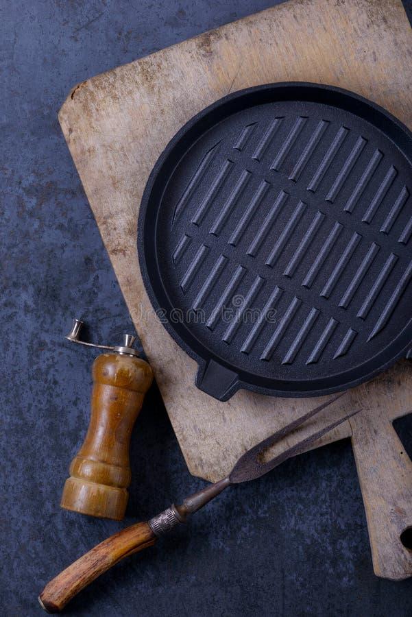 La casserole et la viande vides de gril de fer noir bifurquent, poivrent le dispositif trembleur image stock