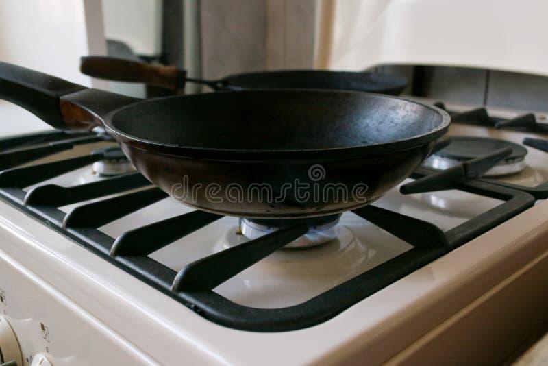 La casserole noire de fonte est sur une cuisinière à gaz photo libre de droits