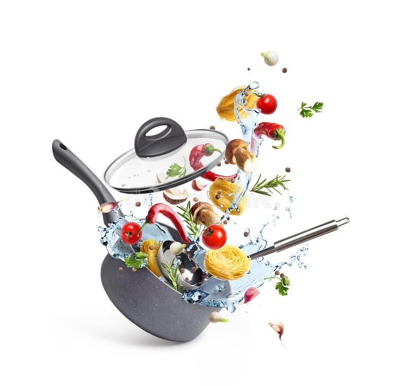 La casseruola con pasta ed i funghi con le verdure ed acqua spruzzano, levitazione, fotografia stock