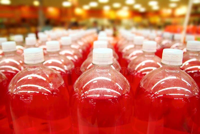 La catena di montaggio liquido rosso della bottiglia rema le righe fotografia stock libera da diritti
