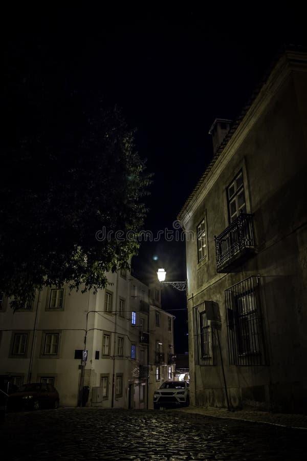 La cattedrale di Lisbona: il paesaggio notturno di Lisbona strada con pietre da pavimentazione illuminate da una vecchia lanterna immagine stock