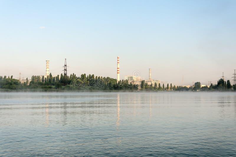 La central nuclear de Kursk reflejó en una superficie tranquila del agua fotografía de archivo