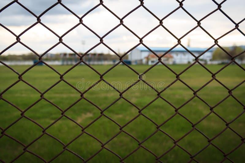 La cerca de la alambrada en los deportes parquea con el campo herboso detr?s de ella foto de archivo