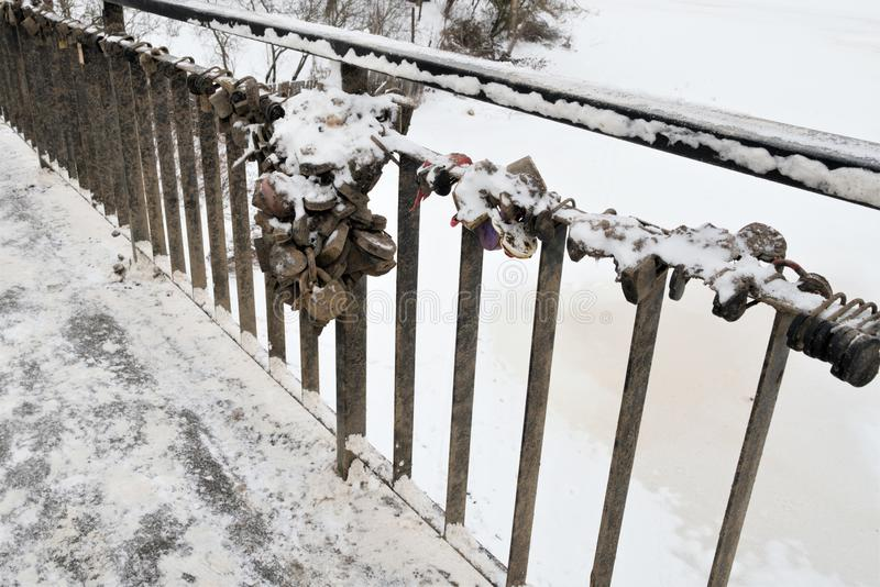 La cerca del puente con los símbolos de una unión fuerte del matrimonio, cerraduras cerradas Invierno imagen de archivo libre de regalías