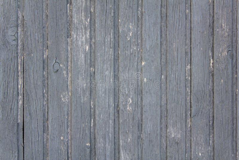 La cerca gris de madera vieja hecha de tablones con la peladura de la pintura, las grietas y los puntos blancos se cierran para a foto de archivo libre de regalías