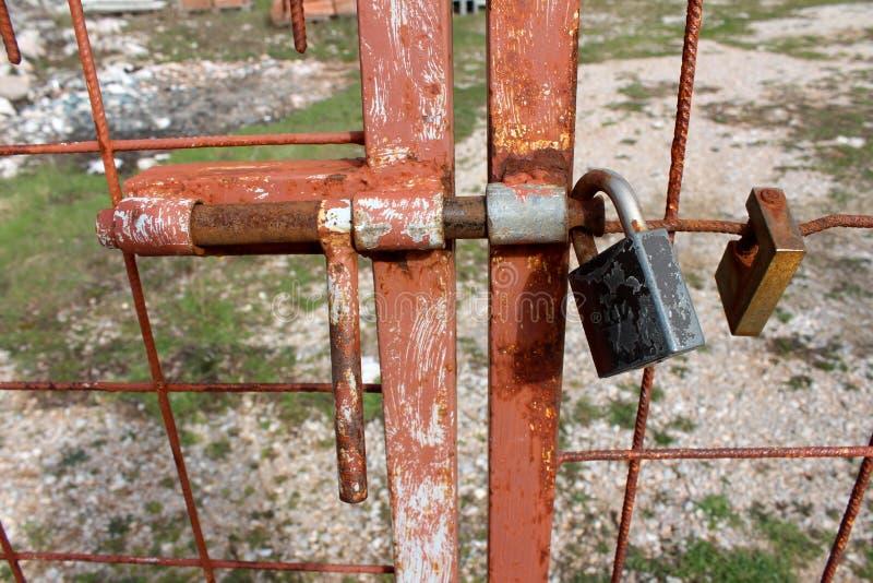 La cerca hecha en casa aherrumbrada del metal con el cierre soldado con autógena se cerró con el candado fotos de archivo libres de regalías