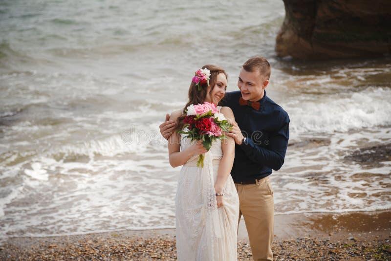 La ceremonia de boda al aire libre de playa cerca del mar, el novio sonriente feliz elegante y la novia están teniendo la diversi foto de archivo libre de regalías