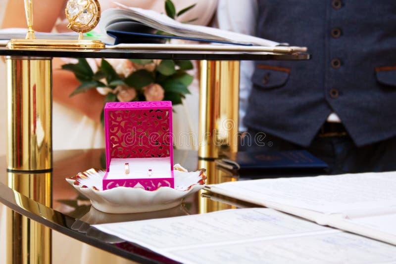La ceremonia de matrimonio, recienes casados es visible en el fondo, foco en los anillos foto de archivo