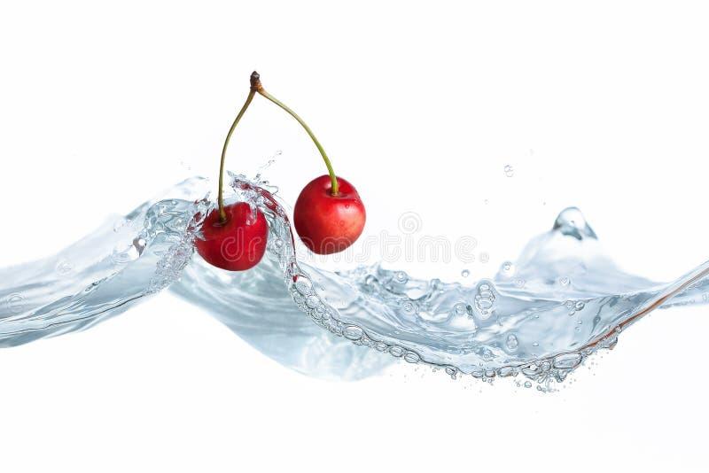 La cereza cayó en chapoteo del agua imagen de archivo