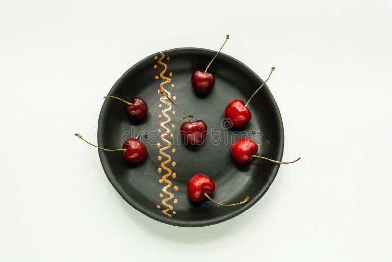La cereza dulce roja miente en una placa negra, un aislador imágenes de archivo libres de regalías