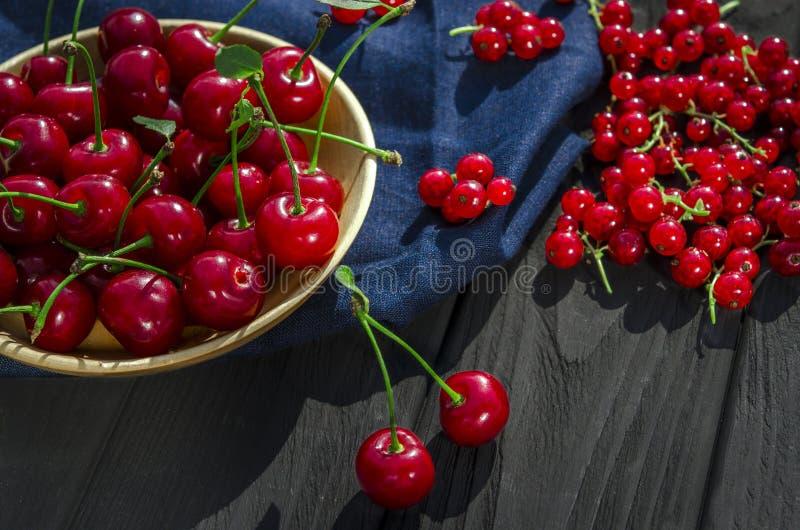 La cereza y las pasas rojas mienten en un fondo de madera negro fotografía de archivo