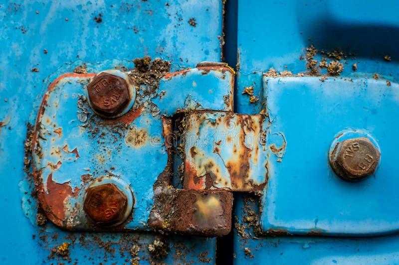 La cerniera di porta di un'automobile blu ha arrugginito dadi abbandonati immagine stock