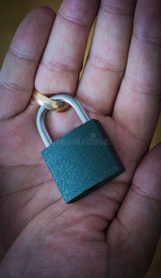 La cerradura en el anillo de bodas en el finger Contrato de matrimonio del concepto Dificultades del divorcio deberes del matrimo imagen de archivo