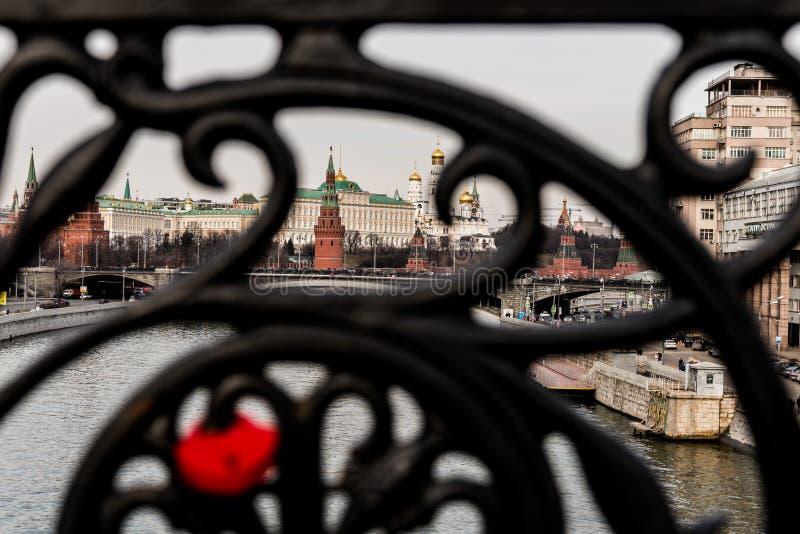 La cerradura en el enrejado forjado del puente está fuera de foco y de una hermosa vista del Kremlin imagenes de archivo
