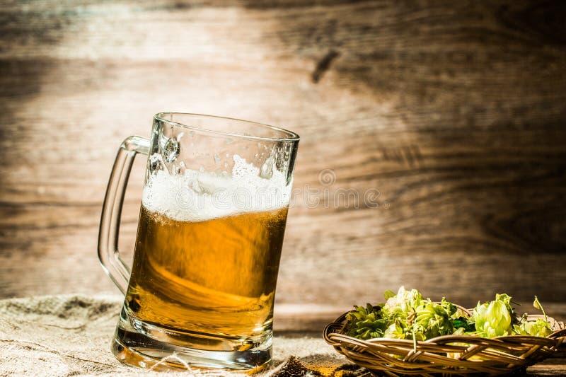 La cerveza en taza grande se coloca en la tabla al lado de salto foto de archivo