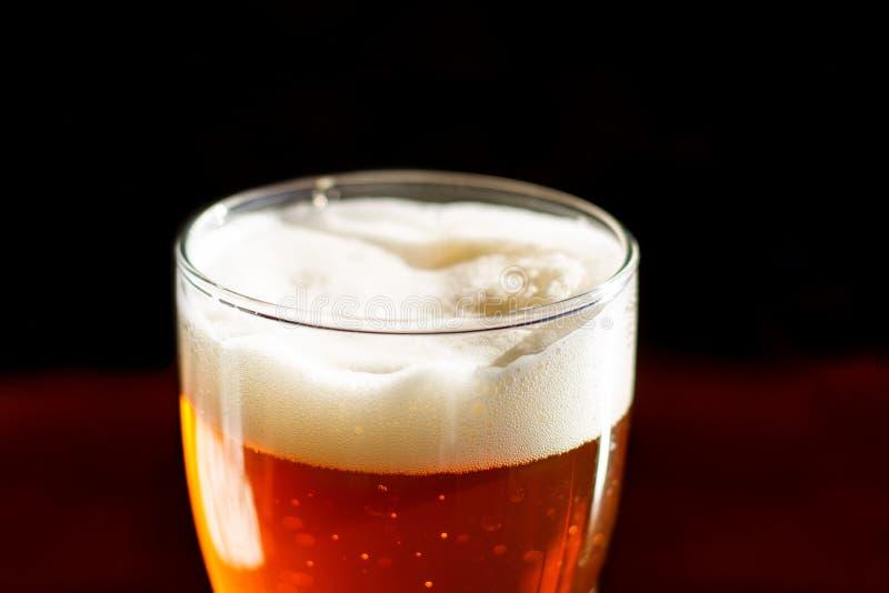 La cerveza en un vidrio en la barra está en el cierre de la tabla para arriba foto de archivo