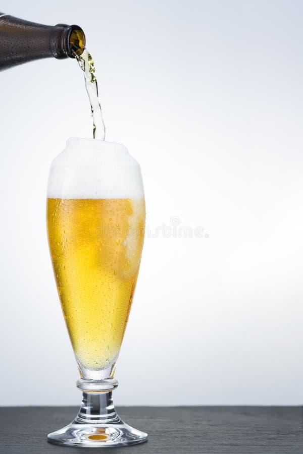 La cerveza está vertiendo en el vidrio fotos de archivo