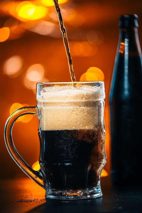 La cerveza oscura se vierte en una taza de cristal foto de archivo libre de regalías