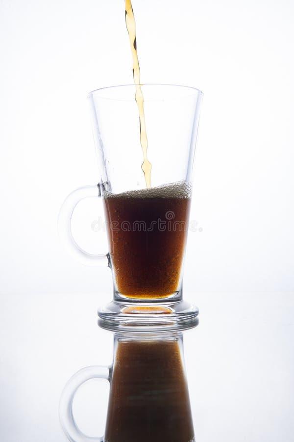 La cerveza oscura se vierte en una taza en un fondo blanco imágenes de archivo libres de regalías