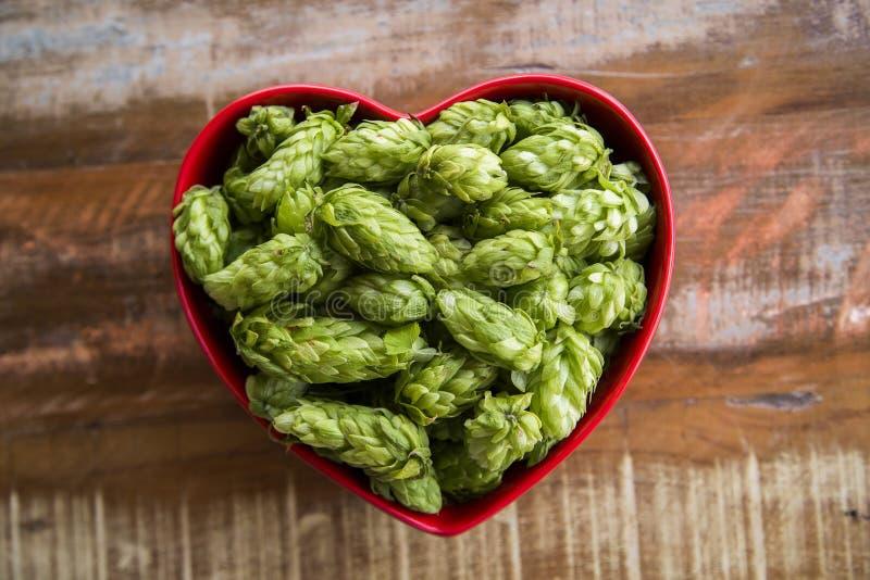 La cerveza que elabora los conos de salto de los ingredientes en corazón rojo rueda en fondo de madera Concepto de la cervecería  fotografía de archivo