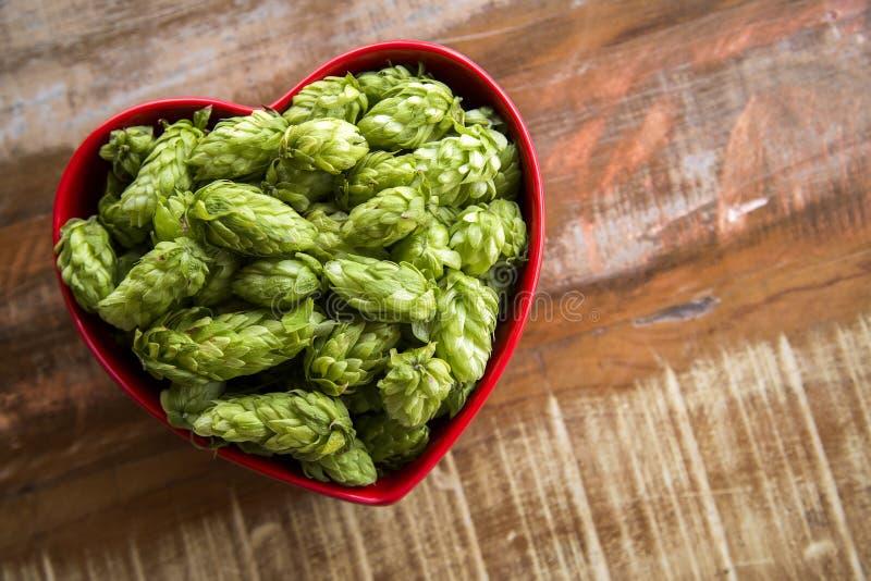La cerveza que elabora los conos de salto de los ingredientes en corazón rojo rueda en fondo de madera Concepto de la cervecería  imágenes de archivo libres de regalías